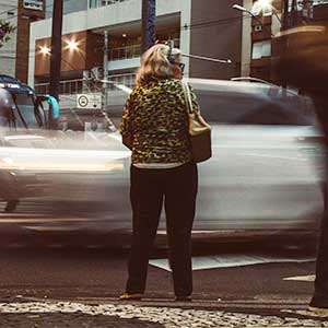 woman waiting to cross a busy street