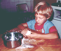 Carma baking a cookie at four years old