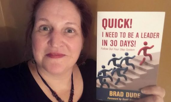 Carma Spence holding a copy of Quick! I Need to Be a Leader in 30 Days!