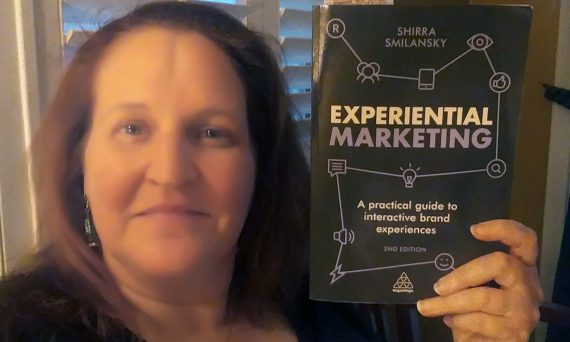Carma Spence holding a copy of Shirra S