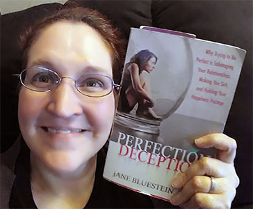 Carma holding a copy of The Perfection Decption